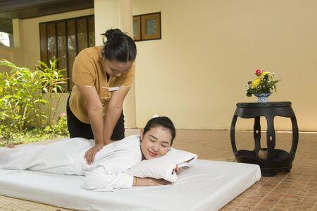 thai yoga: Woman getting Thai massage from professional masseuse Stock Photo