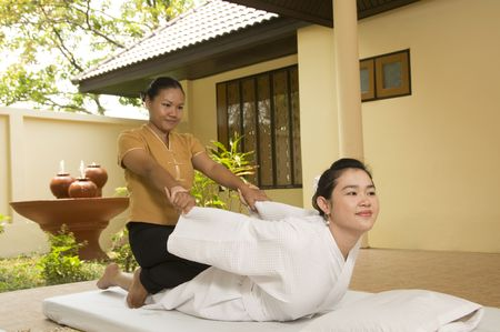 alternative therapies: Woman getting Thai massage from professional masseuse Stock Photo