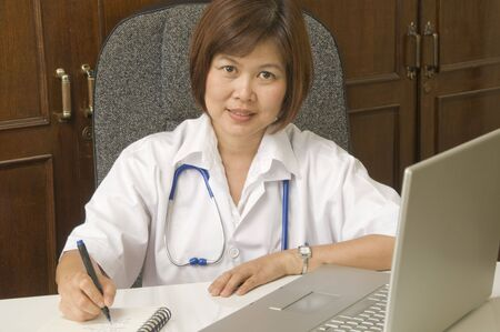 at her desk: Doctor sitting at her desk and writing