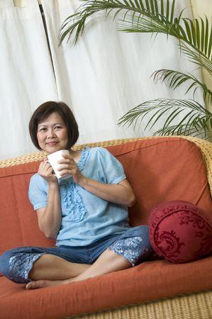 Beautiful young Asian woman having a cup of tea