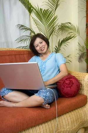 ch: Woman sitting on her sofa and working with computer