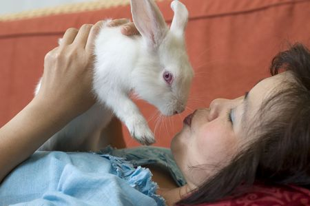 Woman laying down and giving her rabbit a kiss photo