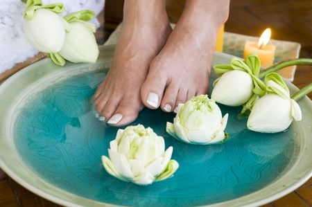 woman foot: Feet enjoy a relaxing aromatherapy foot spa with Lotus flowers Stock Photo