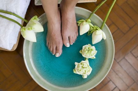 Feet enjoy a relaxing aromatherapy foot spa with Lotus flowers Stock Photo