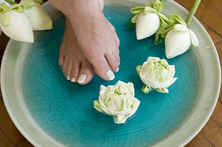 girls bathing: Feet enjoy a relaxing aromatherapy foot spa with Lotus flowers Stock Photo