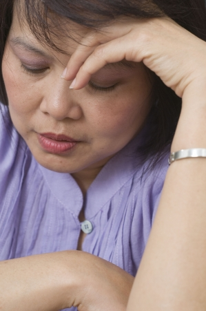 Woman holding her head and feeling depressed Stock Photo