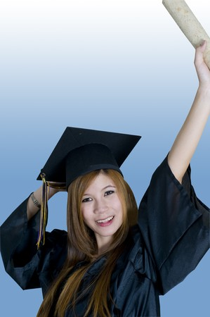 Young woman with graduation cap and gown holding diploma in the air photo