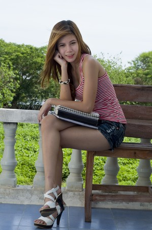 Attractive female student sitting outdoors with her books photo