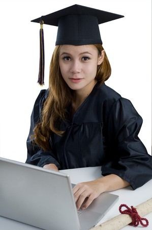 Young woman with graduation cap and gown sitting at desk with computer photo