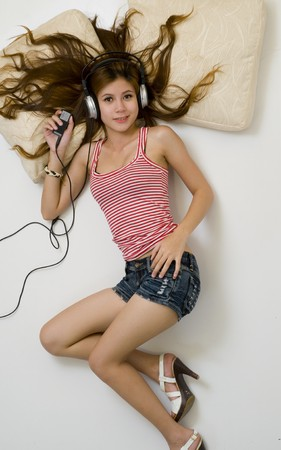 Sexy young girl wearing shorts listening to music on headphones photo