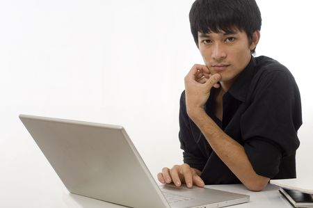 Portrait of a young Asian businessman sitting at desk using computer Stock Photo - 7510354