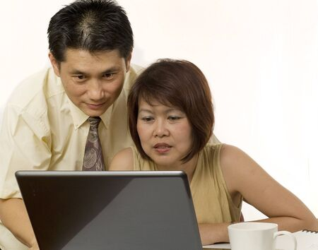 Middle age Asian couple using computer for internet Stock Photo