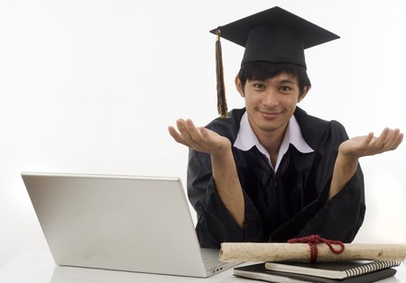 Young man with graduation cap and gown and diploma sitting at computer thinking about his future Stock Photo