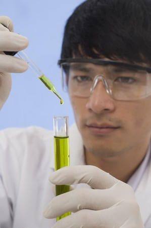 Scientist pouring chemicals in a laboratory Stock Photo - 7510360