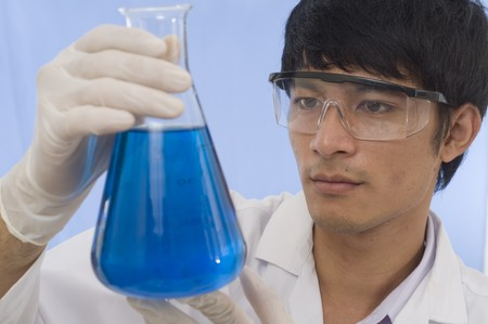 Scientist pouring chemicals in a laboratory photo