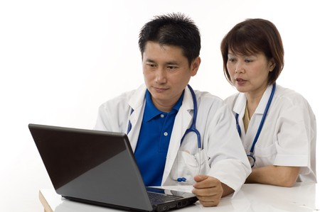 Doctor and Nurse checking patients records on computer photo