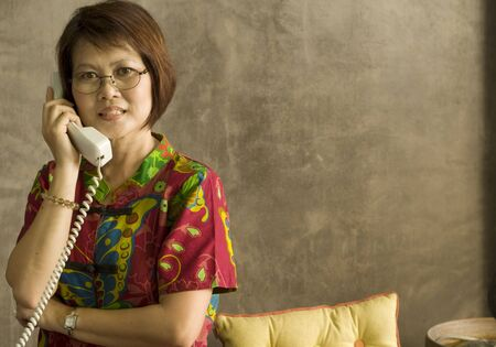 Beautiful mature Asian woman talking on the telephone Stock Photo