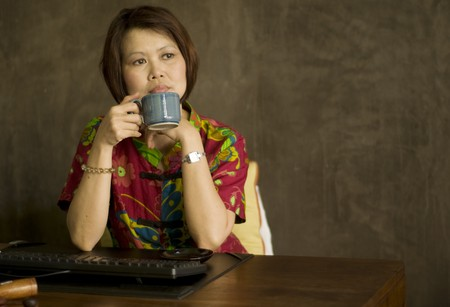 Middle aged Asian woman sitting at her desk with a cup of tea and relaxing photo