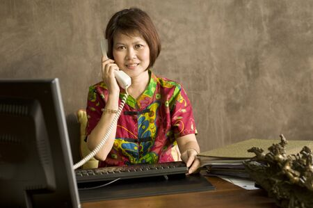 Beautiful mature Asian woman talking on the telephone photo