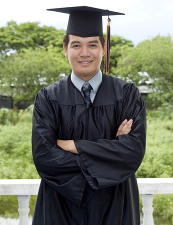 Young Asian man with graduation cap and gown  photo