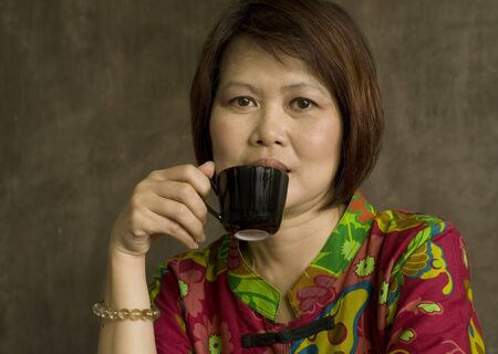 Asian woman relaxing with a cup of coffee photo