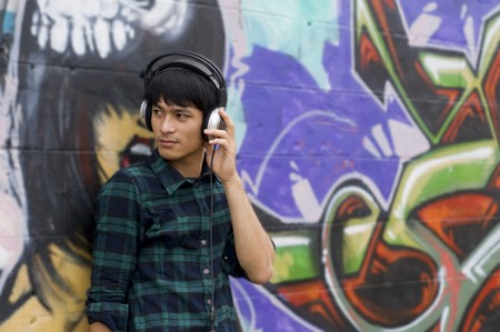 young adult Asian male listening to music on headphones leaning against a graffitti wall Stock Photo