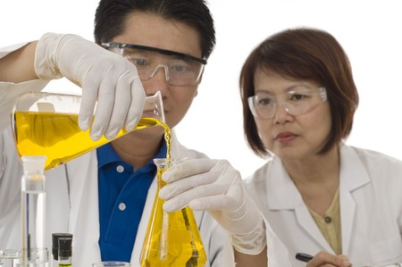 chemist's: Scientist team  pouring chemicals in a laboratory Stock Photo