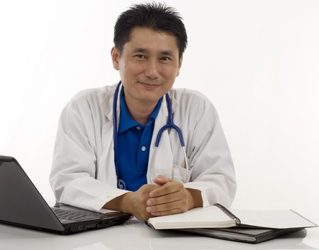 Doctor sitting at his desk and smiling
