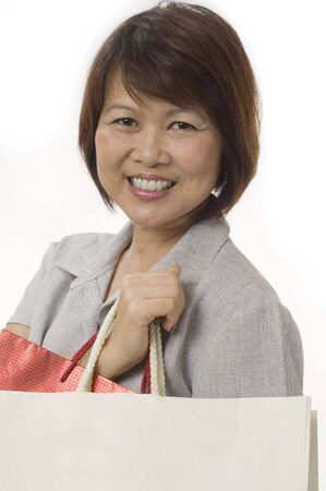 Mature Asian woman with shopping bags isolated on white photo