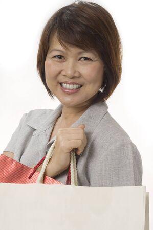 Mature femme asiatique avec des sacs à provisions isolé sur fond blanc  Banque d'images
