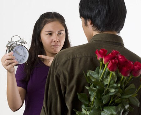 Young Asian couple with man holding flowers behind his back and woman pointing to clock indicating that He is late