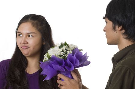 apology: Man offering flowers to his girlfriend who is very upset after arguement
