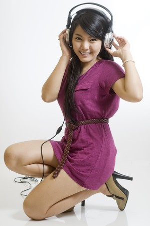 Sexy young girl listening to music on headphones photo
