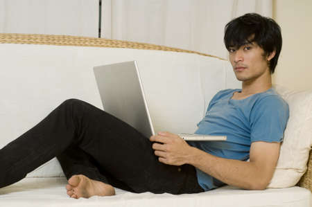 Young Asian man laying on sofa and using computer photo