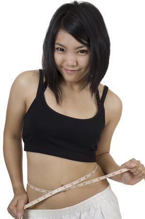 Attractive young Asian girl with measuring tape around her waist photo