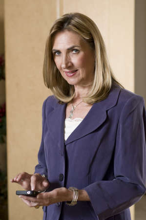 Portrait of a mature businesswoman texting using mobile phone  photo