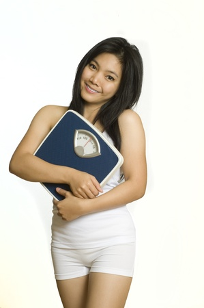 Attractive young Asian girl holding her weight scale happy with her diet==== Stock Photo - 8790949