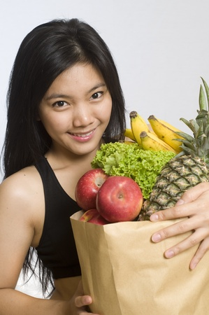 Healthy young girl holding a bag of groceries photo