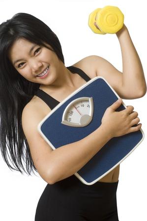 gewicht skala: Attraktive junge asiatische M�dchen mit Waage und Hanteln