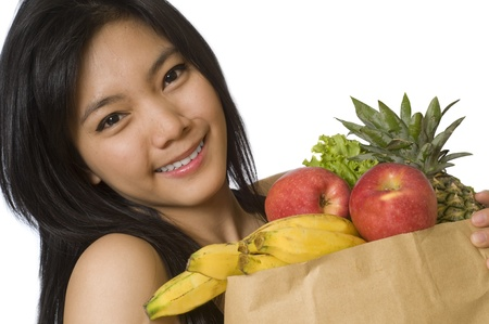 asian produce: Healthy young girl holding a bag of groceries