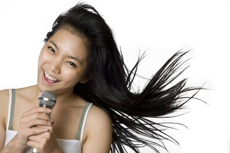 cantando: Joven asi�tica cantando en un micr�fono