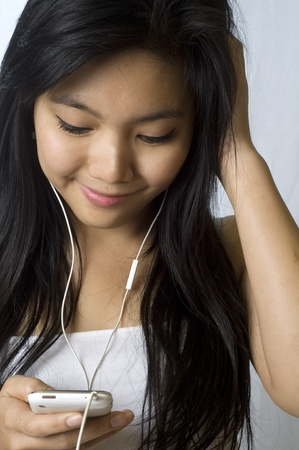 Pretty young Asian girl listening to music on headphones Stock Photo