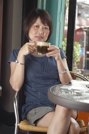 prime adult: Middle aged Asian woman relaxing and drinking coffee
