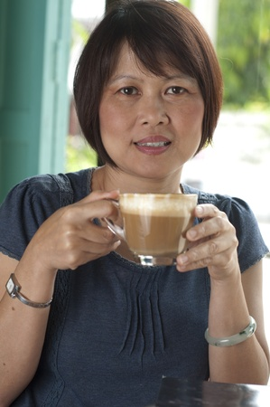 prime adult: Asian woman drinking coffee