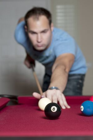 8 ball pool: Young man playing a game of pool Stock Photo