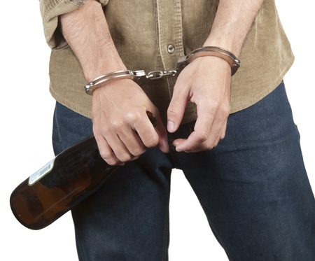 Handcuffed young man with a beer bottle photo