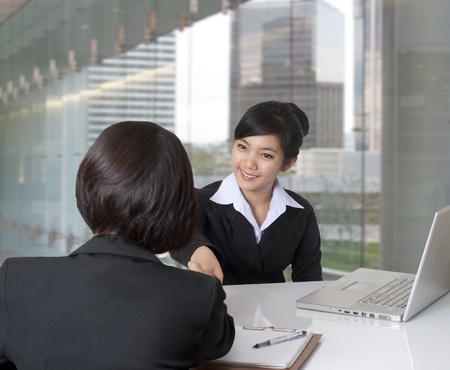 entrevista de trabajo: Dos mujeres dándose la mano en la oficina