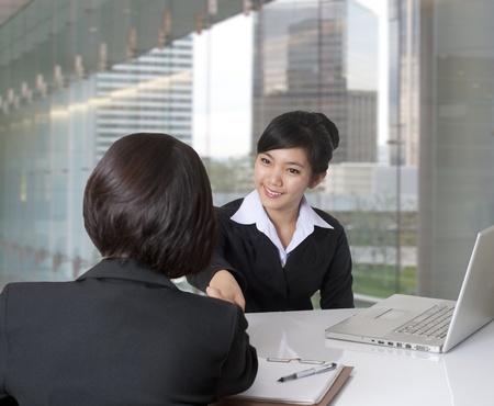 Twee vrouwen handen schudden in het kantoor Stockfoto
