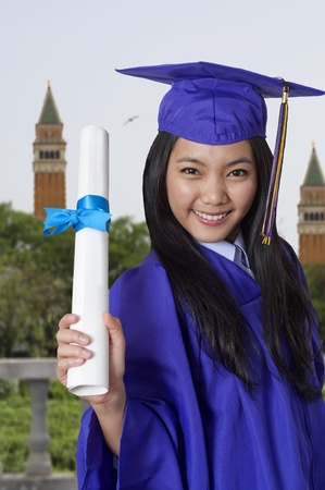 Young woman with graduation cap and gown holding her diploma Stock Photo