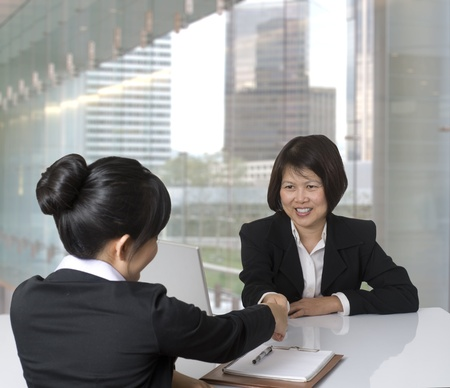 interview: Portrait of Asian businesswoman shaking hands with colleague